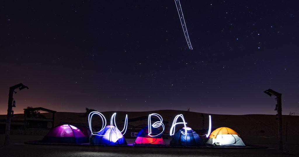 Lightpainting mit Taschenlampe - das  Wort Dubai mit vor Zelten in der Wüste